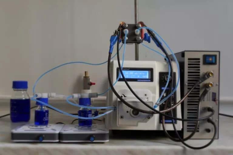 Установка для тестирования ячейки ванадиевой проточной батареи. МЭБ закреплена на штативе над перистальтическим насосом. Емкости заполнены ванадиевым электролитом (до начала процесса зарядки батареи